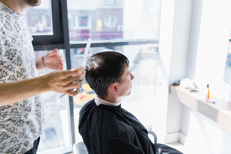 A professional hairstylist with a comb and scissors in his hand styling the wet black and short hair of the man in a royalty free stock photo