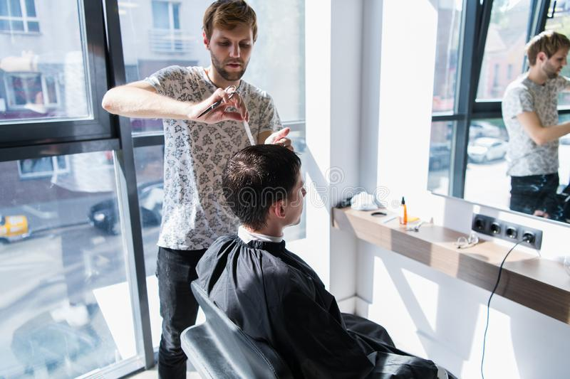 A professional hairstylist with a comb and scissors in his hand styling the wet black and short hair of the man in a stock image