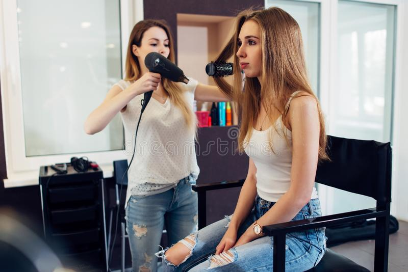 Professional hairstylist using hairdryer and round brush to style long fair hair of the female customer in beauty salon royalty free stock photos