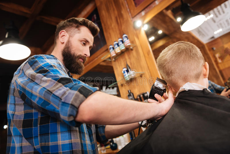 Professional handsome barber holding a hair cutting machine. Doing a haircut. Professional nice handsome barber holding a hair cutting machine and working with a royalty free stock photo