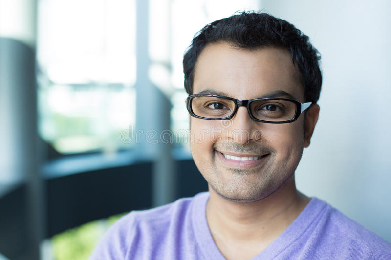 Professional headshot man. Closeup headshot portrait, smiling happy handsome man in purple sweater v-neck, wearing black glasses, isolated inside office