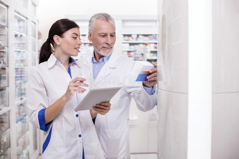 Mature male doctor assisting pharmacist stock photography