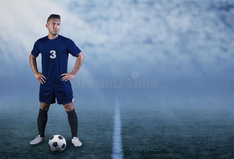 Professional Hispanic Soccer Player on the field ready to play. The portrait of a Professional Hispanic soccer/football player standing on the field with a ball royalty free stock photography