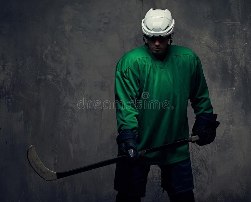 Professional hockey player trains in full equipment with gaming stick against a gray background. royalty free stock photos