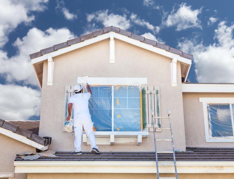Professional House Painter Painting the Trim And Shutters of A H. Ome royalty free stock photo