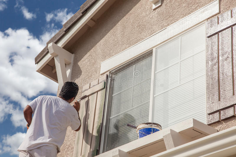 Professional House Painter Painting the Trim And Shutters of A H. Ome royalty free stock photos