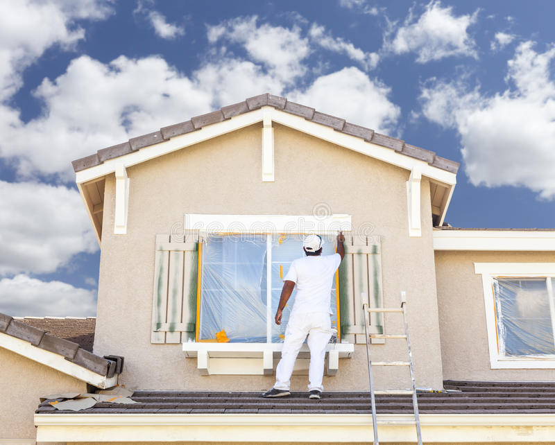 Professional House Painter Painting the Trim And Shutters of Home. Busy House Painter Painting the Trim And Shutters of A Home stock photo