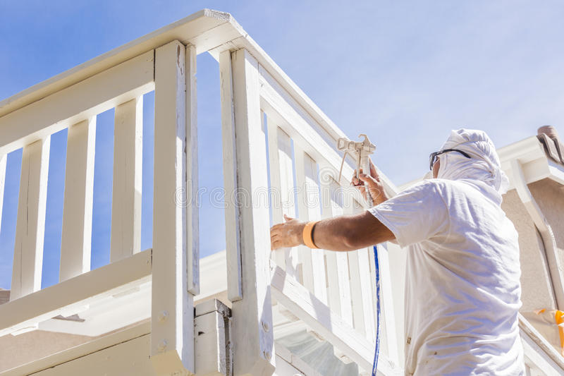 Professional House Painter Spray Painting A Deck of A Home. House Painter Wearing Facial Protection Spray Painting A Deck of A Home royalty free stock photo
