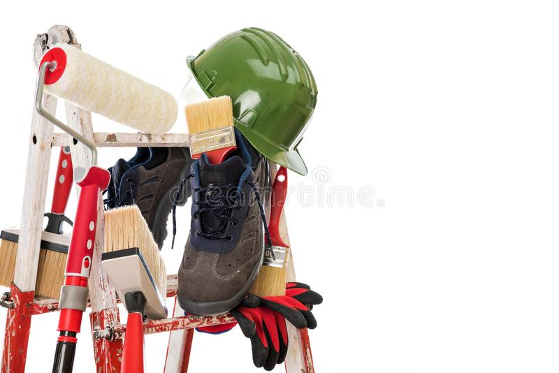 Professional house painter, tools and work equipment. Work tools and safety equipment for professional house painter on a sturdy metal ladder. Isolated on white royalty free stock image