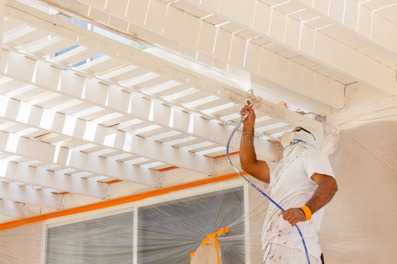 Professional House Painter Wearing Facial Protection Spray Paint. Ing Deck of A Home stock image