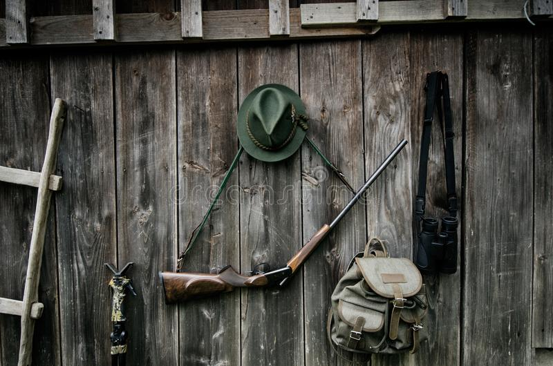 Professional hunters equipment for hunting. Rifle, hat, bag and others on a wooden black background. stock photography
