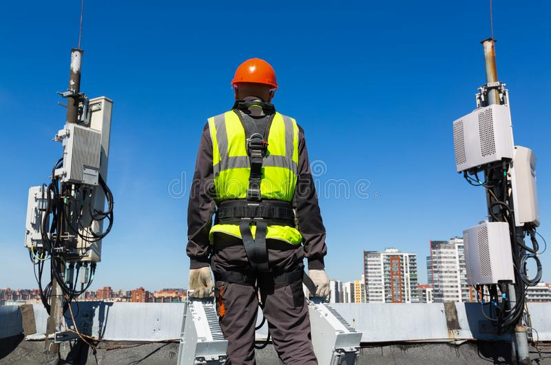 Professional industrial climber in helmet and uniform holds telecomunication equipment in his hand and antennas of GSM royalty free stock photo