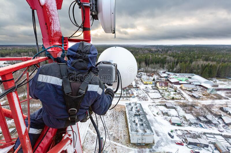 Professional industrial climber in uniform and climber equipment on the telecommunication tower is installing outdoor stock images