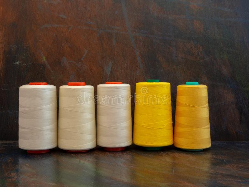 Professional industrial cones of sewing threads laying and standing on a dark background. Front view studio shot. royalty free stock image
