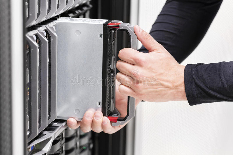 IT professional installs server cluster in large datacenter. It engineer or consultant working with installation of a blade server cluster in data rack. Shot in stock photo