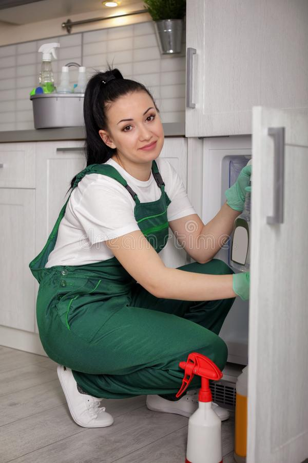 Professional janitor cleaning modern fridge. In kitchen royalty free stock photos