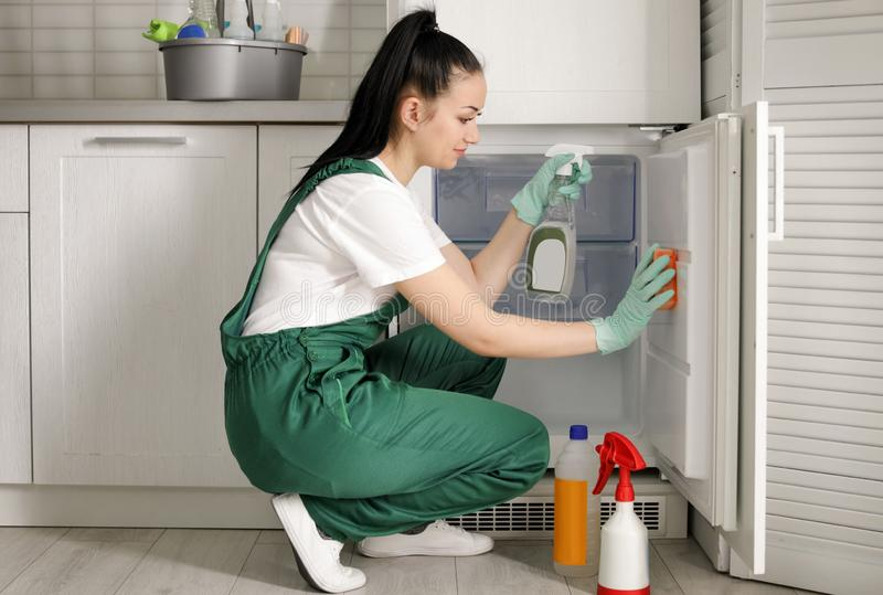 Professional janitor cleaning modern fridge. In kitchen stock image