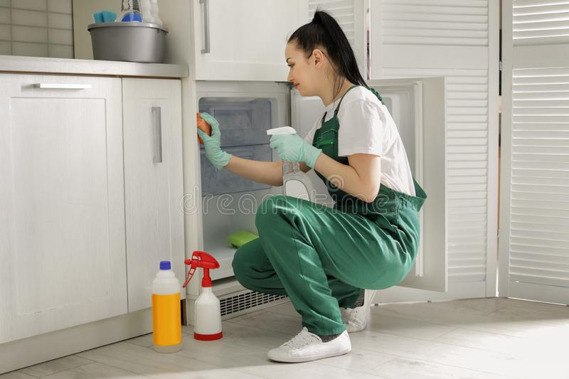 Professional janitor cleaning modern fridge. In kitchen royalty free stock image