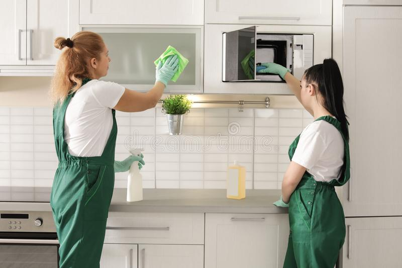Professional janitors cleaning kitchen with supplies. Indoors royalty free stock photography