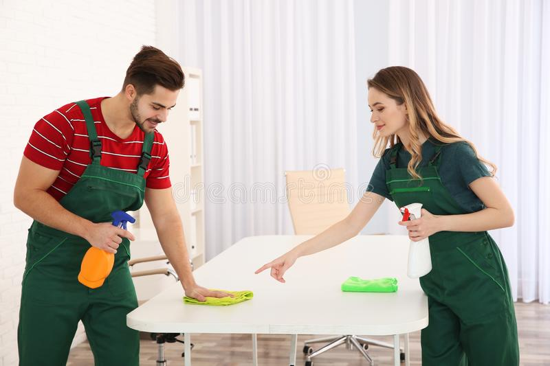 Professional janitors cleaning table. Hired help. Professional janitors cleaning table in office. Hired help stock images