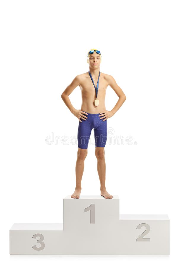Professional junior swimmer winner on the first place of a pedestal. Full length portrait of a professional junior swimmer winner on the first place of a stock photography