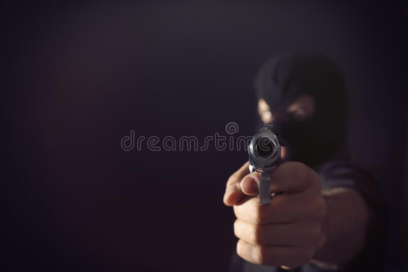 Professional killer on black background, focus on gun. Space for text stock photo