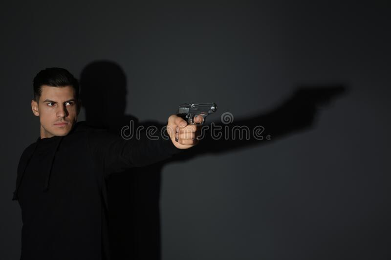 Professional killer with gun on black background stock photography