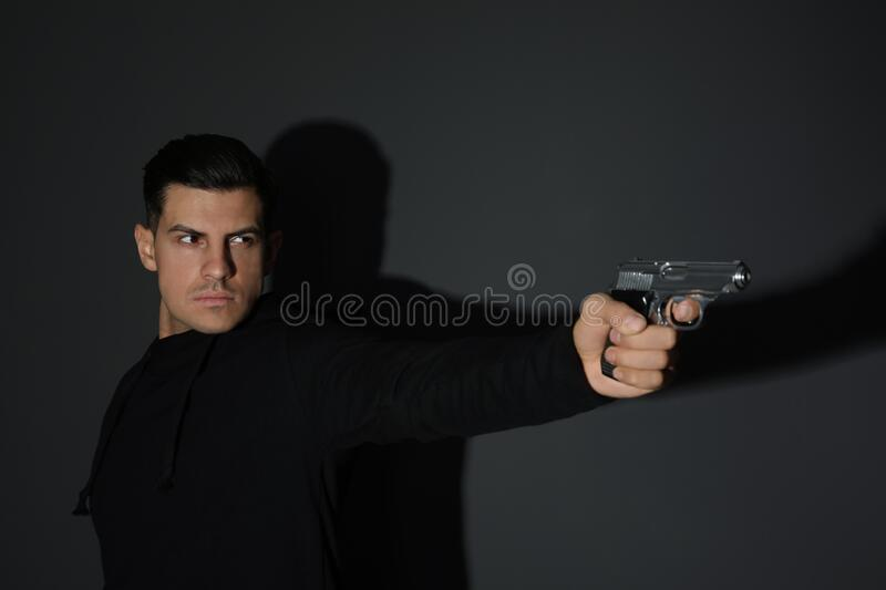 Professional killer with gun on black background stock images