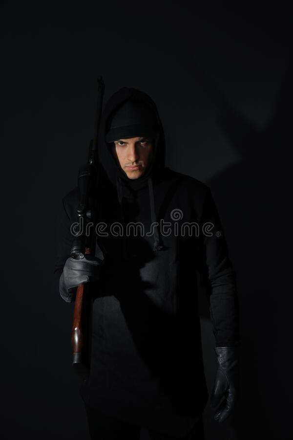 Professional killer with sniper rifle on black background stock photos