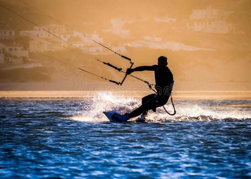 Professional kiter makes the difficult trick on a beautiful back royalty free stock photography