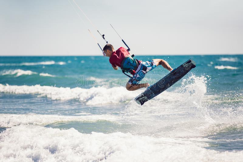 Kiter makes the difficult trick on a beautiful background. Kitesurfing Kiteboarding action photos man among waves. Professional kiter makes the difficult trick royalty free stock images