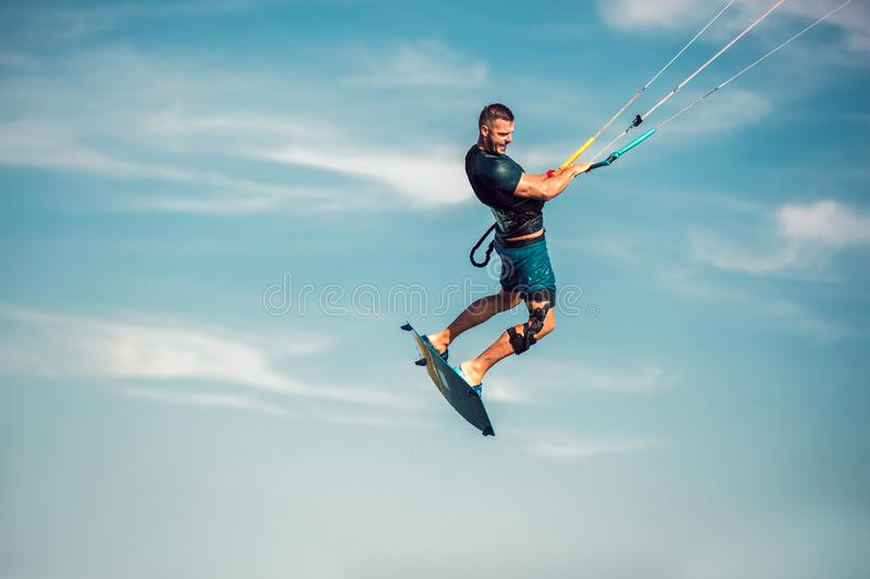 Kiter makes the difficult trick on a beautiful background. Kitesurfing Kiteboarding action photos man among waves. Professional kiter makes the difficult trick royalty free stock photos