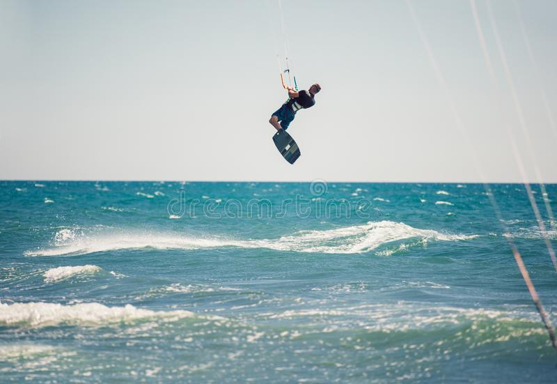 Kiter makes the difficult trick on a beautiful background. Kitesurfing Kiteboarding action photos man among waves. Professional kiter makes the difficult trick royalty free stock image