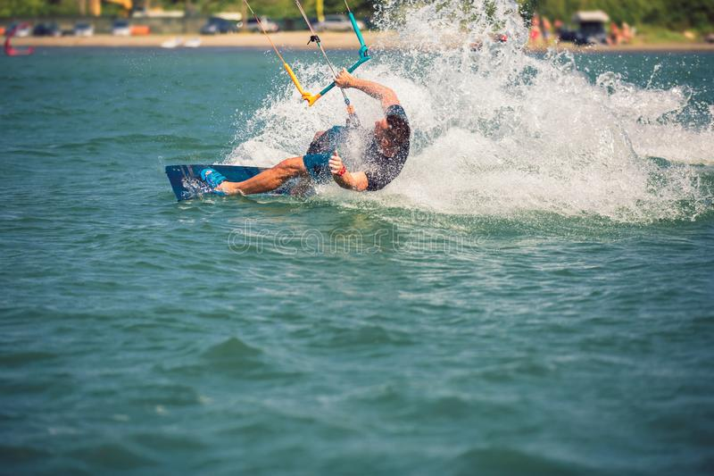 Kiter makes the difficult trick on a beautiful background. Kitesurfing Kiteboarding action photos man among waves royalty free stock image