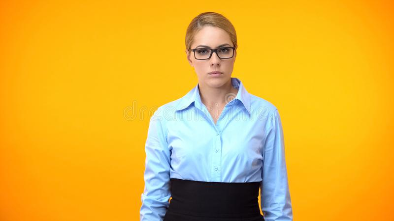 Professional lady boss looking camera on orange background, confident worker royalty free stock image