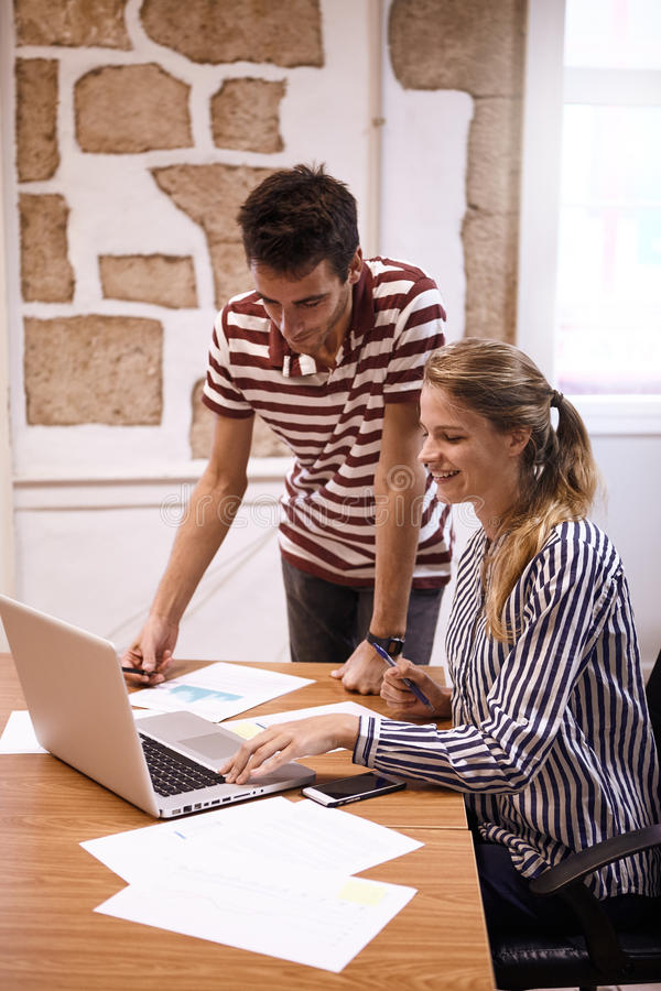Professional lady showing something to man. Professional young business lady showing a young men something on a laptop they are sharing while he is standing next stock photography