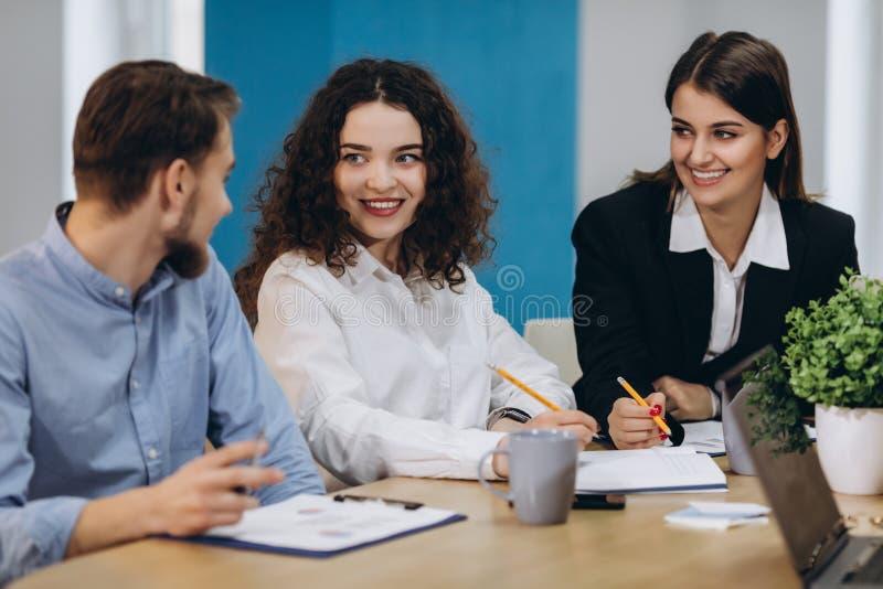 professional lag Lyckliga idérika ungdomarsom arbetar i lag, medan vara på kontoret arkivfoto