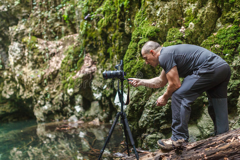 Professional landscape photographer by the lake. Professional landscape photographer with camera on tripod by the lake royalty free stock photos