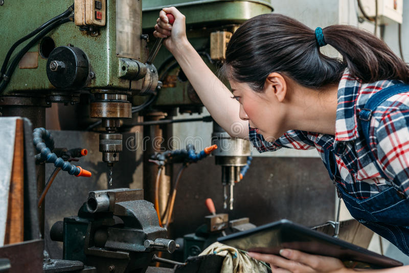 Worker adjust machine to correct position. Professional lathe female worker holding mobile digital tablet computer and adjust drilling machine to correct royalty free stock image