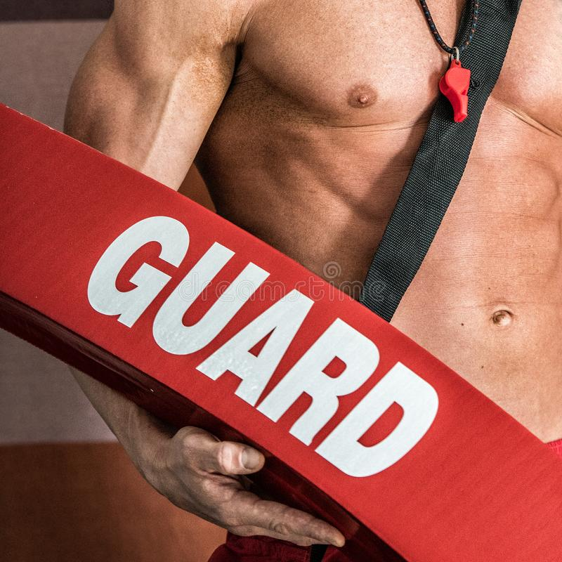 Professional lifeguard with strong body holding red safety tube and whistle stock image