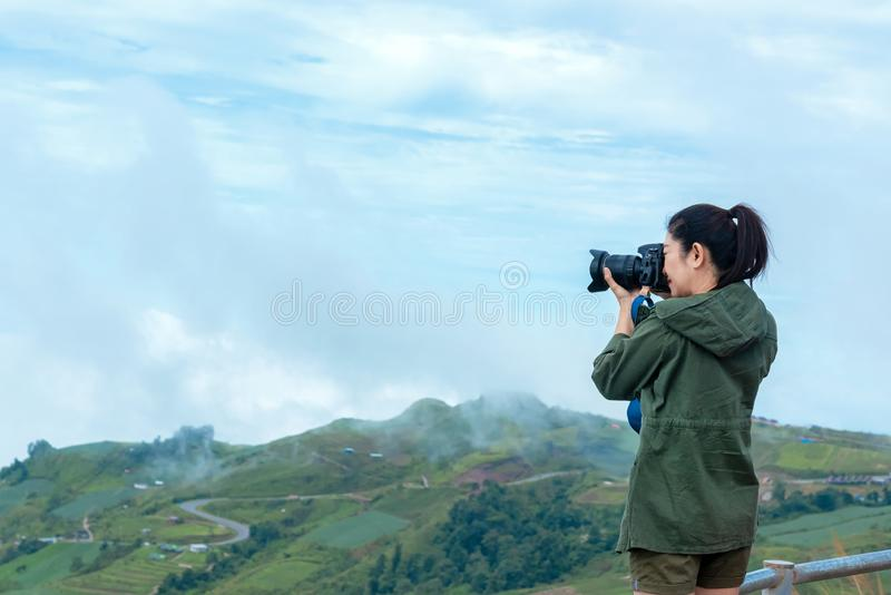Professional lifestyle woman photographer taking with prime lens outdoor in the mountain, winter season stock image