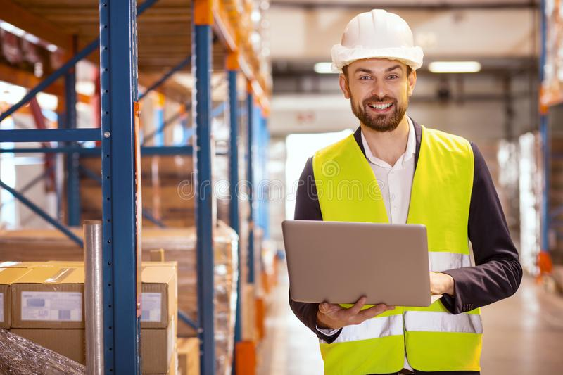 Cheerful nice man dealing with logistics. Professional logistics manager. Cheerful nice man smiling while dealing with logistics system in the storehouse royalty free stock image