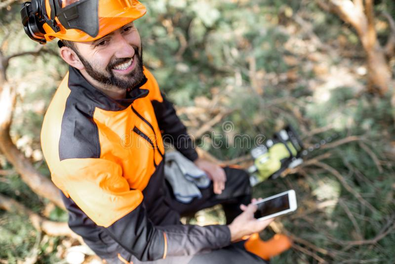 Professional lumberman resting with phone in the forest stock photos