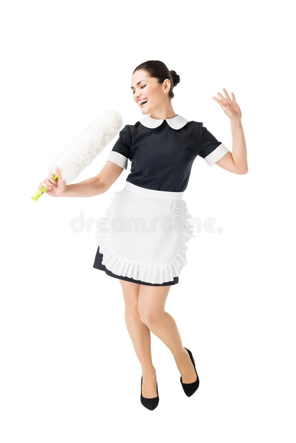 Professional maid in uniform having fun and singing in duster royalty free stock photography