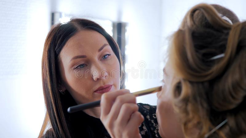 Professional make-up artist applying cream base eyeshadow primer to model eye royalty free stock photos