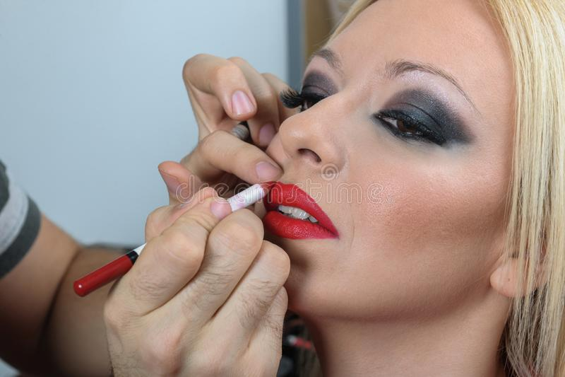Professional make up artist applying lipstick to a young model face royalty free stock photography