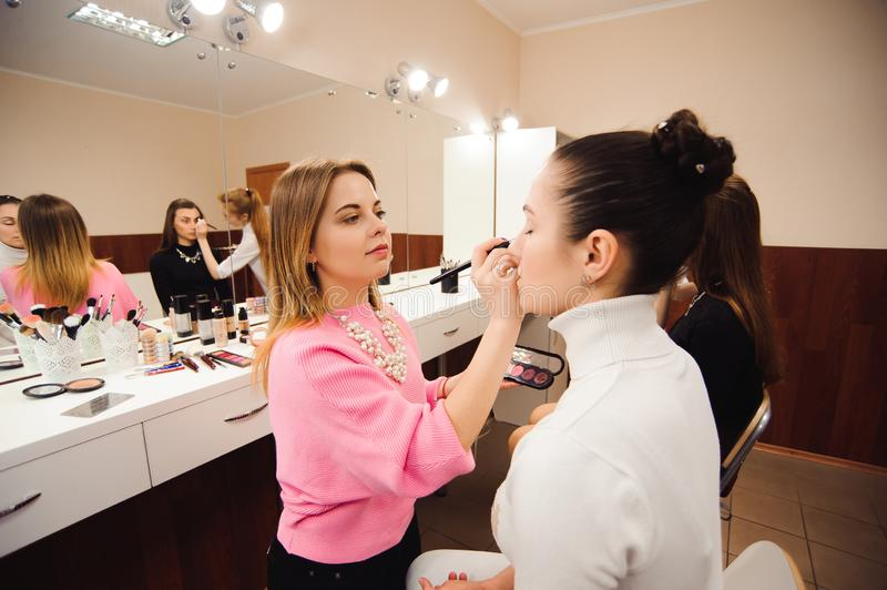 Professional make-up artists work with beautiful young women. School of professional make-up royalty free stock photos