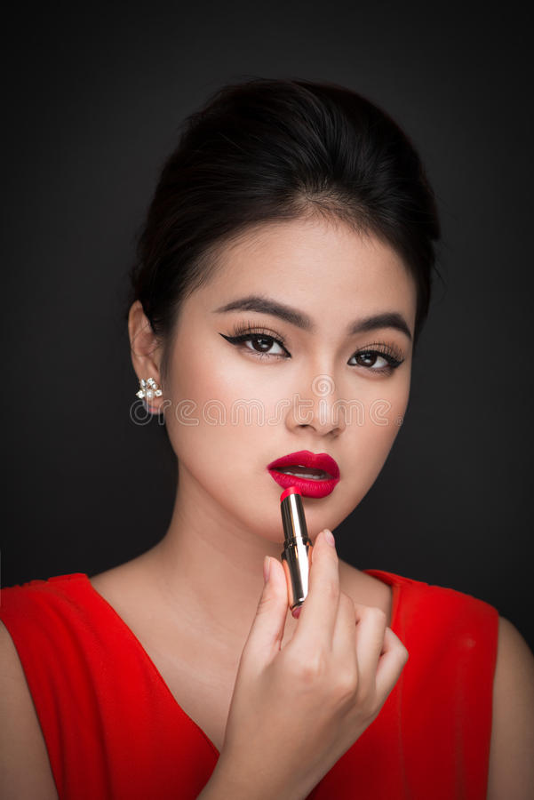 Free Professional Make-up. Attractive Asian Model Applying Red Lipstick. Stock Photography - 94606652