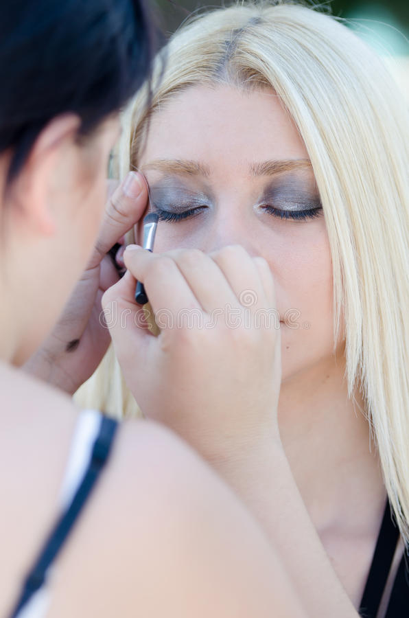Professional makeup artist applying make up outdoor. Professional makeup artist applying make up on a beautiful young blonde model face for a photo shoot royalty free stock photos