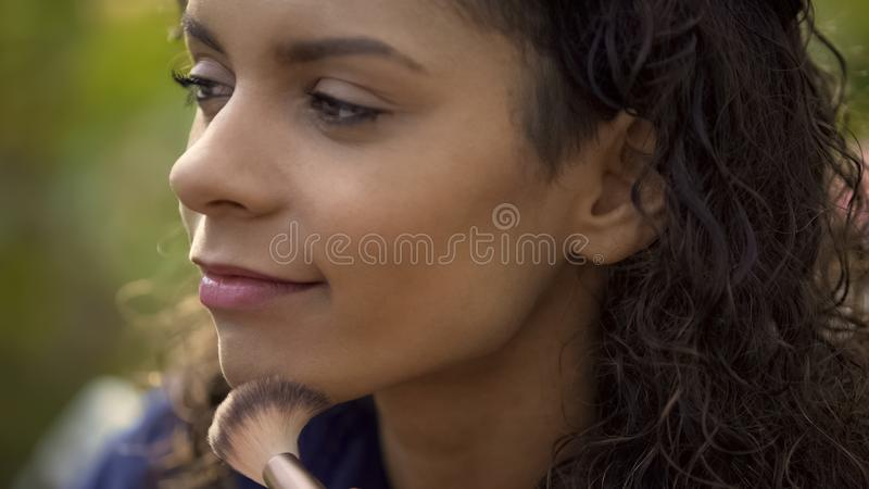 Professional makeup artist evens up model skin tone with brush, movie shooting royalty free stock image